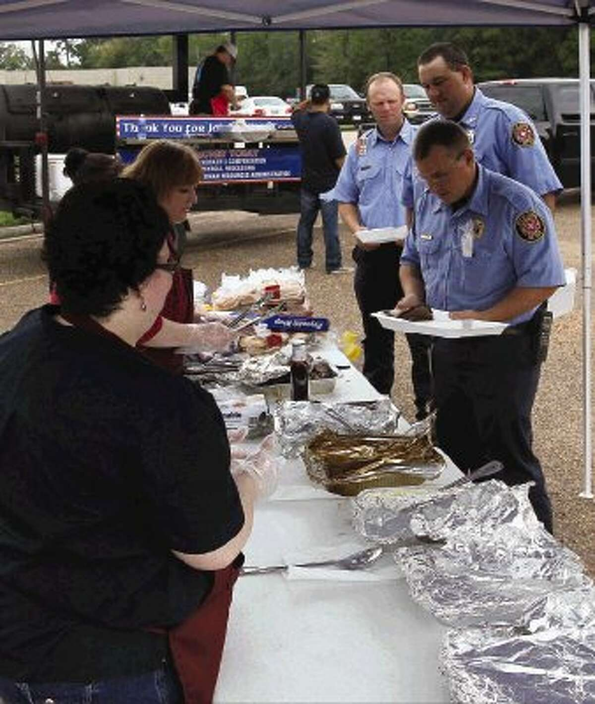 Conroe Police Officers Thomas Chavis, Phillip Johnson and Andy Bay receive food during a lunch for Conroe law enforcement and emergency workers Tuesday. Questco Companies sponsored the barbecue lunch for around 100 people in honor of law enforcement and emergency personnel involvement in the Sept. 11, 2001, terrorist attacks, which occurred 12 years ago today. Questco employees also donated several stuffed animals for emergency workers, police officers and firefighters to give to children they come in contact with while working.