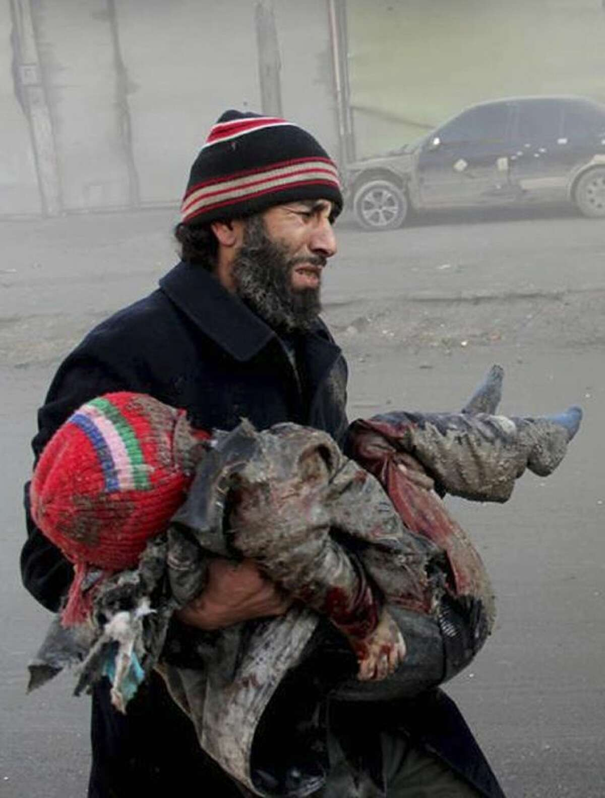 In this Sunday citizen journalism image provided by Aleppo Media Center, AMC, which has been authenticated based on its contents and other AP reporting, a Syrian man cries while holding the body of child who was killed following a Syrian government airstrike in Aleppo, Syria.