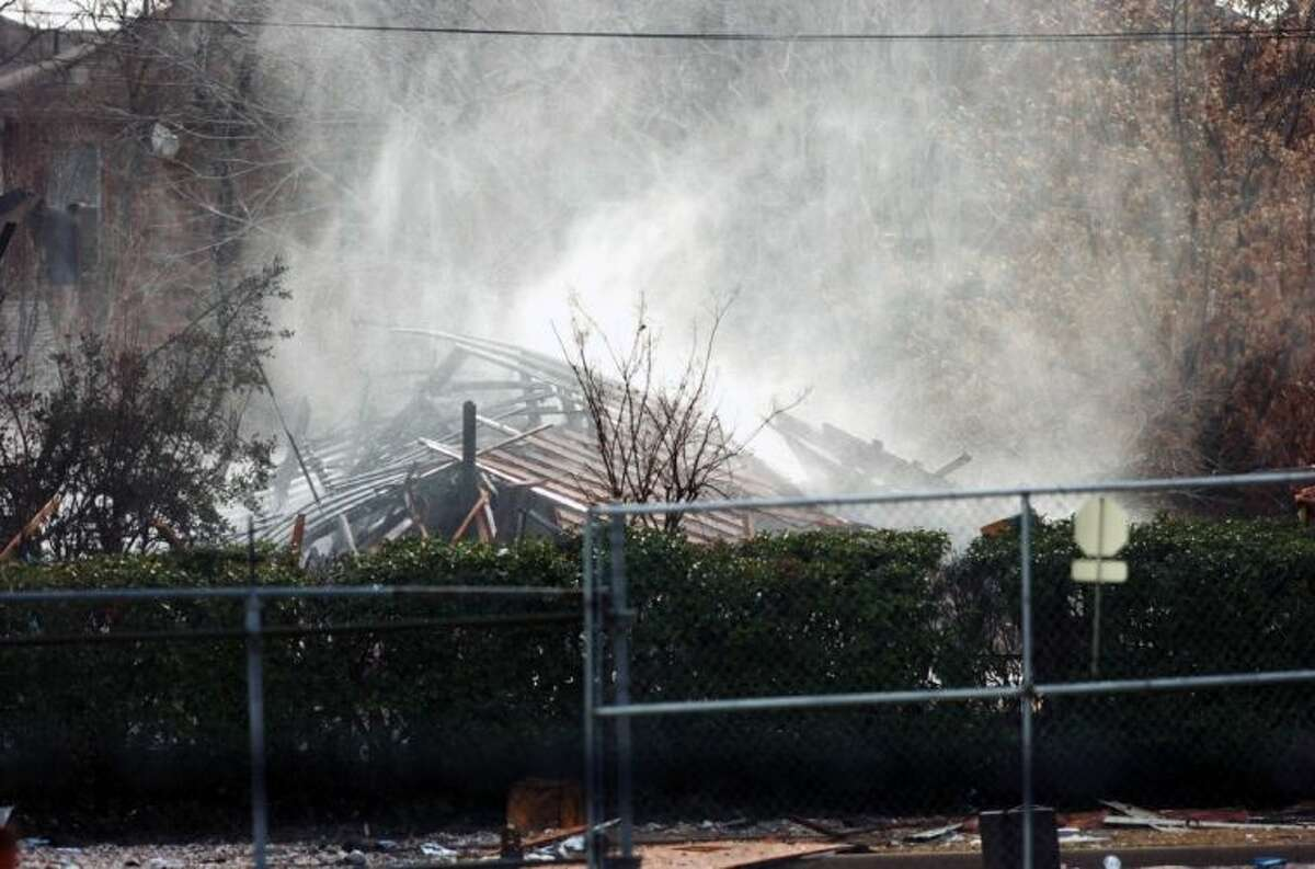 Firefighters hose down the smoldering remains Friday in Lewisville. An explosion Friday in a North Texas neighborhood leveled a home that is part of a local nonprofit's affordable housing program, injuring at least three men and scattering debris.