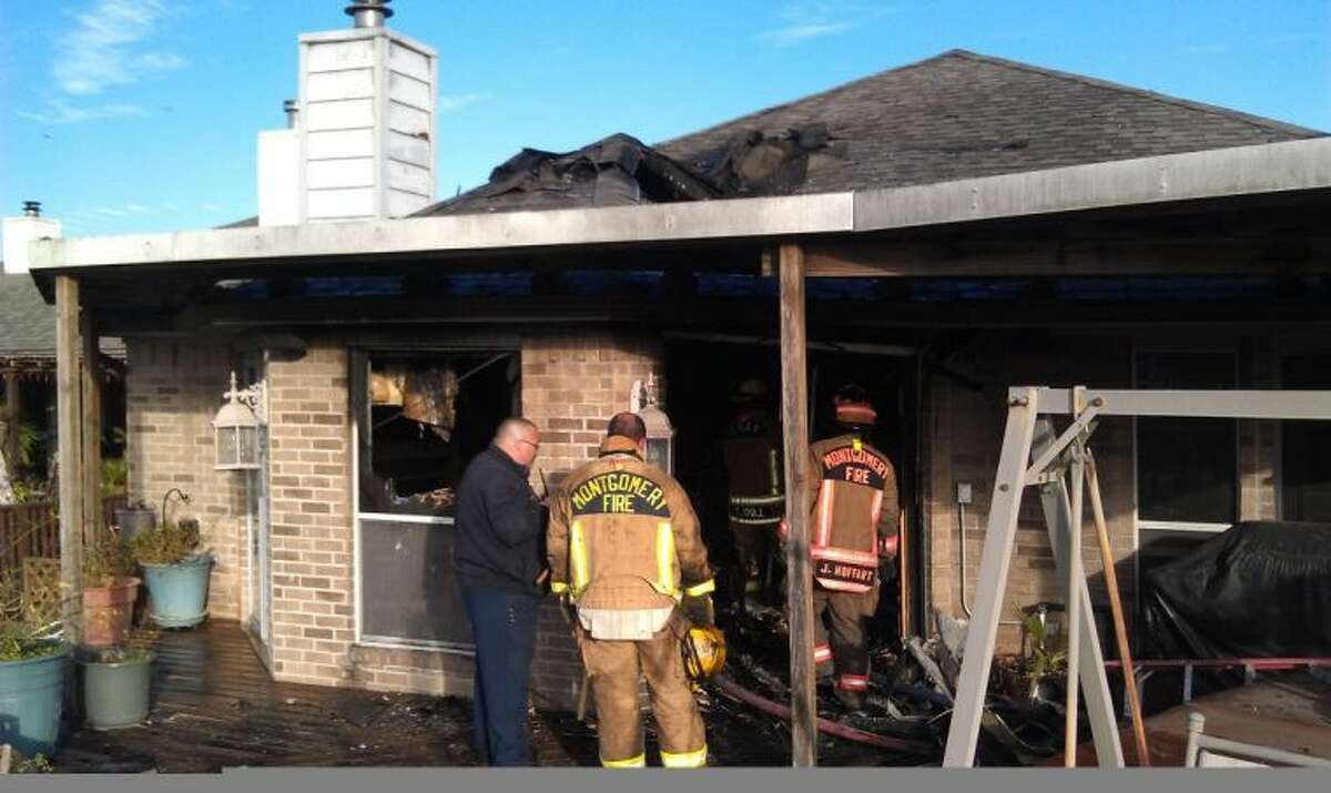 Firefighters from the North Montgomery Volunteer Fire Department and Montgomery FD examine the damage created by the fire Thursday in the Point Aquarius subdivision. A female homeowner suffered severe burns when an oxygen mask she was wearing caught fire.
