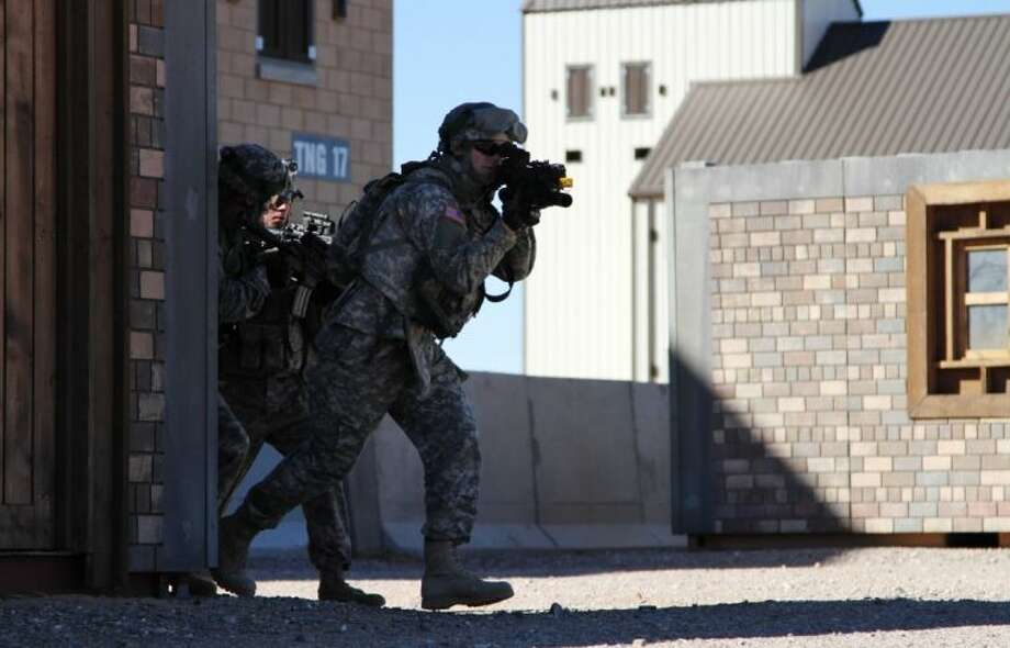 Two soldiers move out of a building during a training exercise in Ft. Bliss, Texas, Wednesday, Jan. 23, 2013. The army is rolling out a new training platform that allows the integration of live units, simulators and computer generated forces. It is expected to allow cheaper, more frequent training. (AP Photo/Juan Carlos Llorca) Photo: Juan Carlos Llorca