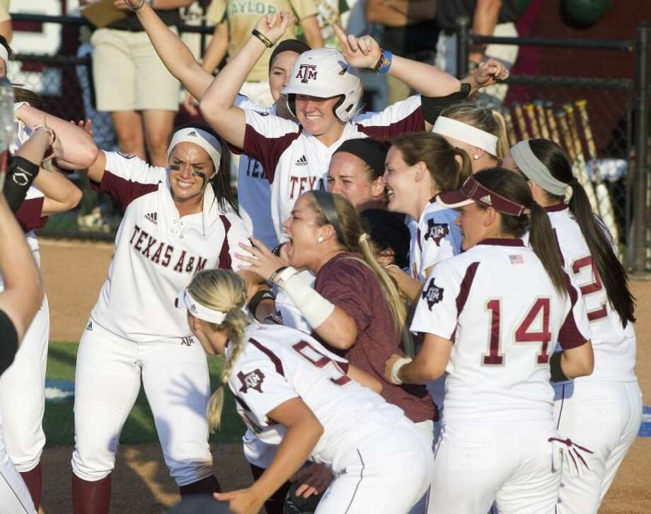 Members of the Texas A&M softball team wait at home plate to greet teammate Cali Lanphear after she hit a game-ending home run against Baylor. Photo: Stuart Villanueva