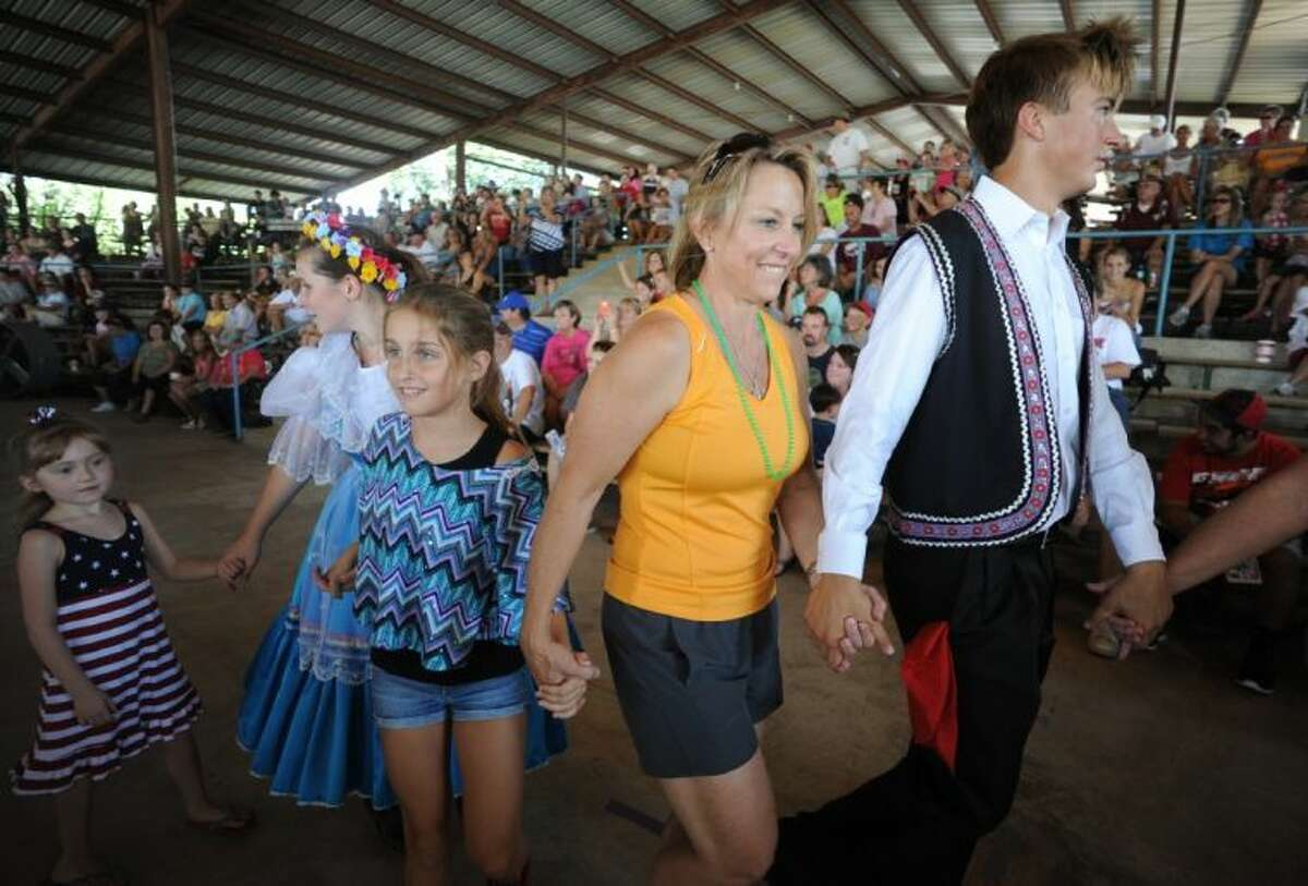 In this Saturday, Sept. 1, 2012 photo, people dance with members of the West High School Junior Historian Czech Dancers during the annual Westfest. This weekend the town is holding the signature celebration of its Czech heritage - the first Westfest since a deadly fertilizer plant explosion tore through the small Central Texas community in April 2013.
