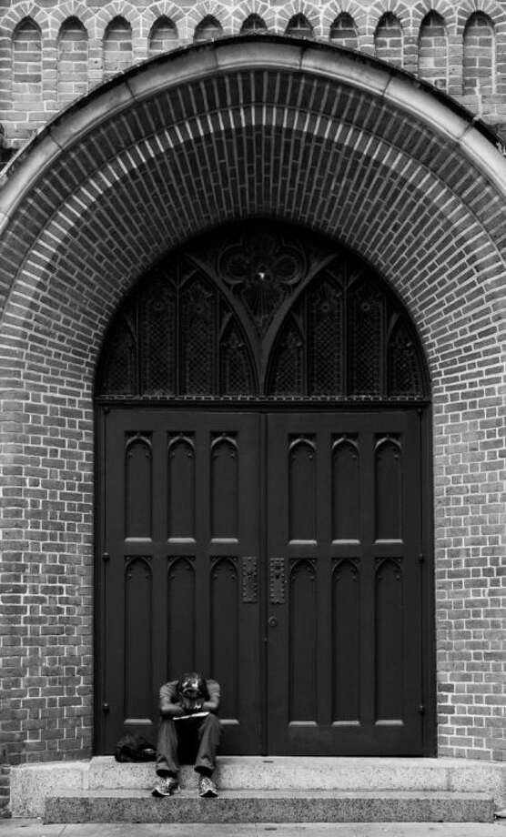 This black and white street photography was taken September 2013 at a church in downtown Houston by area resident Ansel Arnold of an anonymous man resting under a large brick archway. Photo: Reader Photo By Ansel Arnold