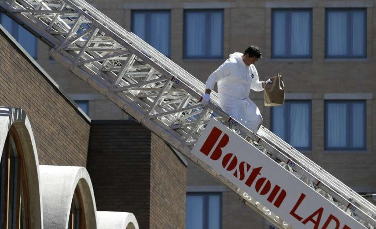 An FBI investigator walks down a fire truck ladder with a bag from the top of a building at the corner of Boylston Street and Fairfield Street Wednesday in Boston. Investigators in white jumpsuits fanned out across the streets, rooftops and awnings around the blast site in search of clues.