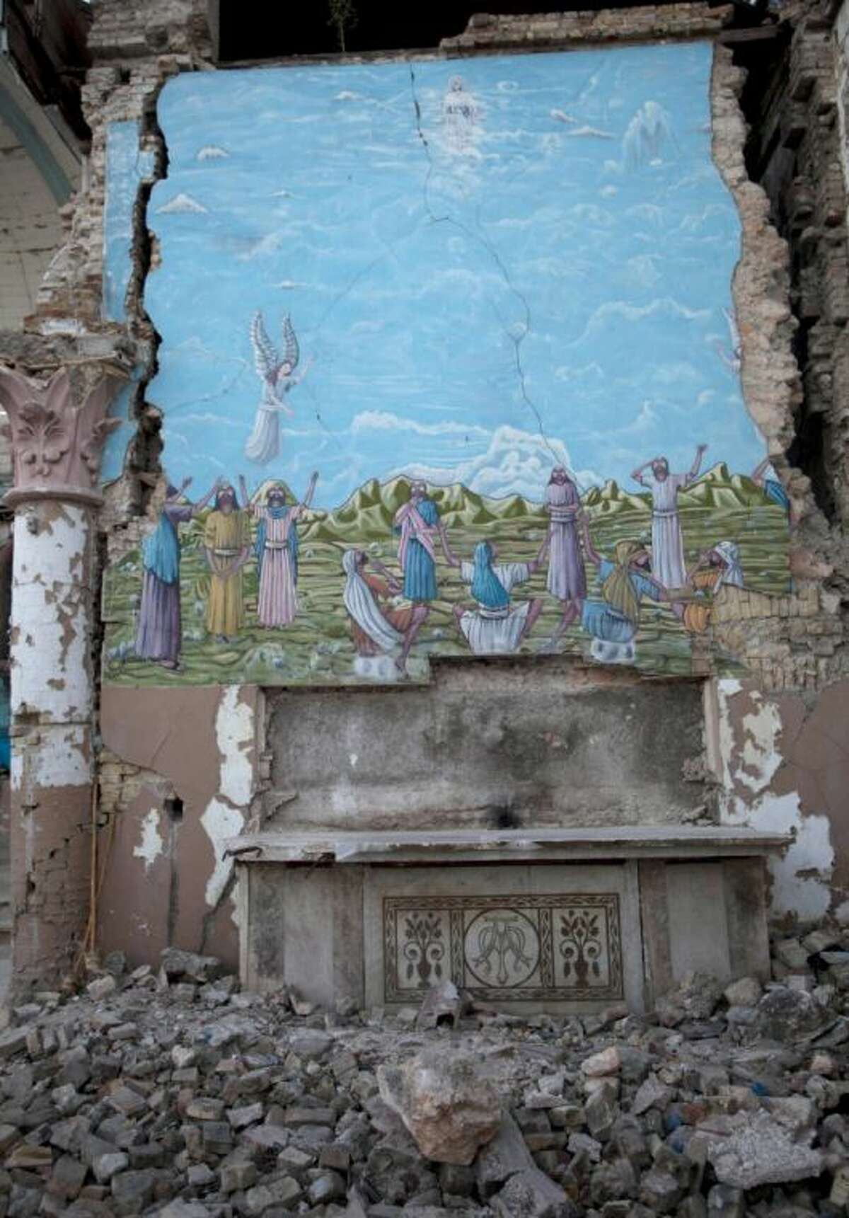 A mural featuring the Resurrection of Jesus Christ bears the signs of earthquake damage 3 years after a 7.0 earthquake struck, leveling a large part of the Santa Ana Catholic church, in Port-au-Prince, Haiti, Saturday.