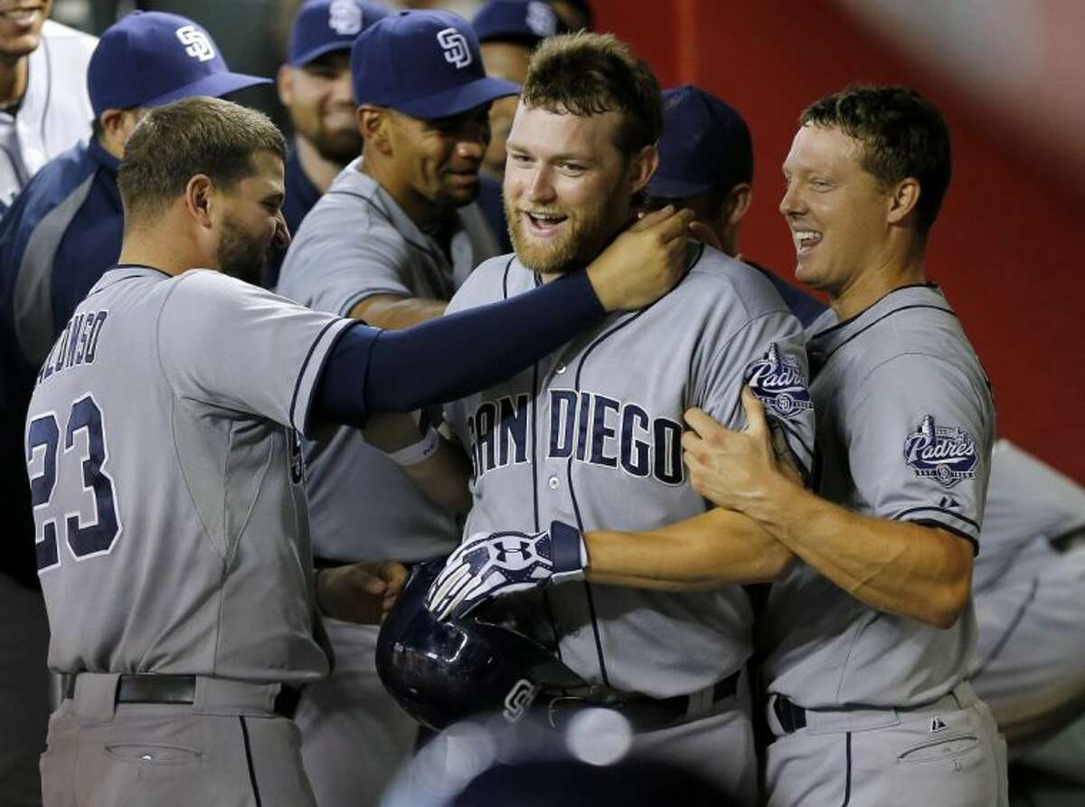 San Diego Padres players grab pitcher Andrew Cashner in the dugout after first ignoring him following his solo home run in the sixth inning against the Arizona Diamondbacks on Saturday in Phoenix. It was the Conroe High School graduate's first major league homer.