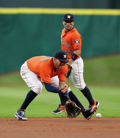 Astros shortstop Carlos Correa fields Mike Trout's grounder during the first inning Saturday. Correa aggravated a shoulder injury in Friday's loss to the Angels but was back out on the field Saturday at Minute Maid Park. Photo: Karen Warren, Staff Photographer / 2016 Houston Chronicle
