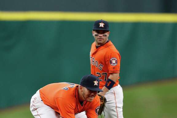 Astros shortstop Carlos Correa fields Mike Trout's grounder during the first inning Saturday. Correa aggravated a shoulder injury in Friday's loss to the Angels but was back out on the field Saturday at Minute Maid Park.