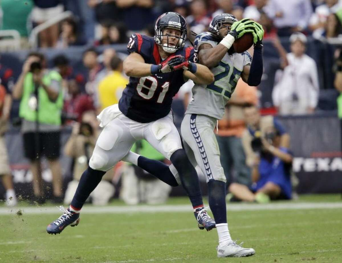 Seattle Seahawks cornerback Richard Sherman intercepts the ball in front of the Houston Texans' Owen Daniels in the fourth quarter. Sherman scored on the play.