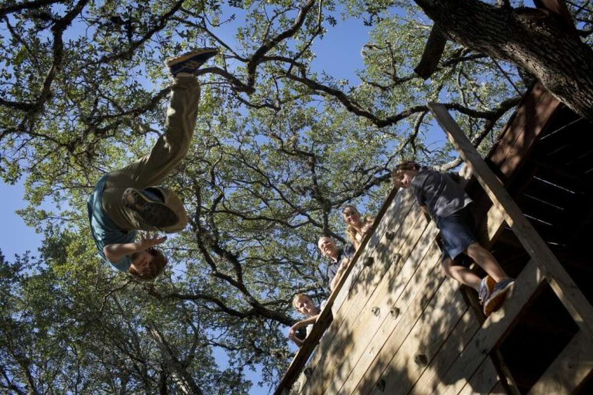 In this Aug. 25 photo, Paxton Wolf, 12, practices falling onto an airbag while his family watches from a climbing wall at Steve Wolf's Stunt Ranch in Austin. The Wolf family worries their income is too high to qualify for new tax credits implemented under the Affordable Care Act.