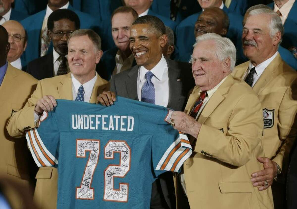 President Obama receives a Dolphins jersey from the 1972-73 unbeaten NFL champions, including Bob Griese, left, coach Don Shula and Larry Csonka, right.