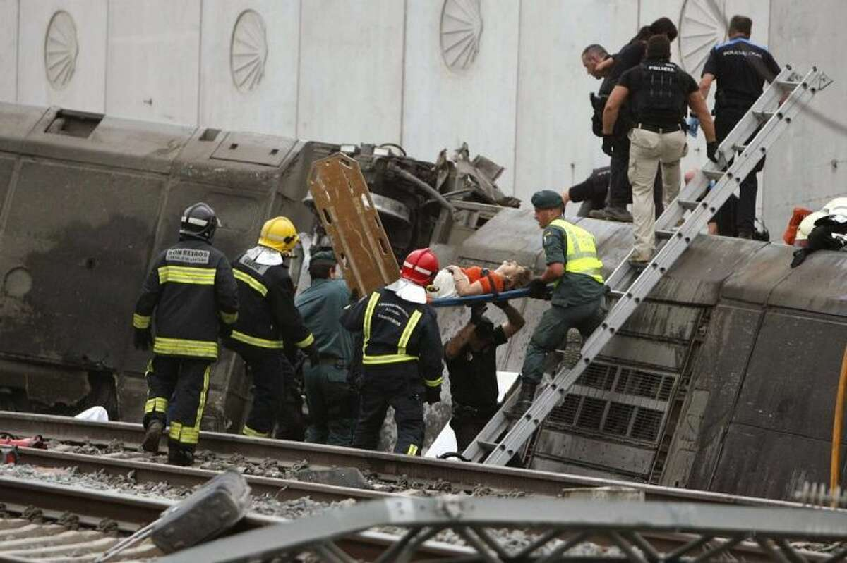 A woman is evacuated by emergency personnel at the scene of a train derailment in Santiago de Compostela, Spain, on Wednesday. A train derailed in northwestern Spain on Wednesday night, toppling passenger cars on their sides and leaving at least one torn open as smoke rose into the air.