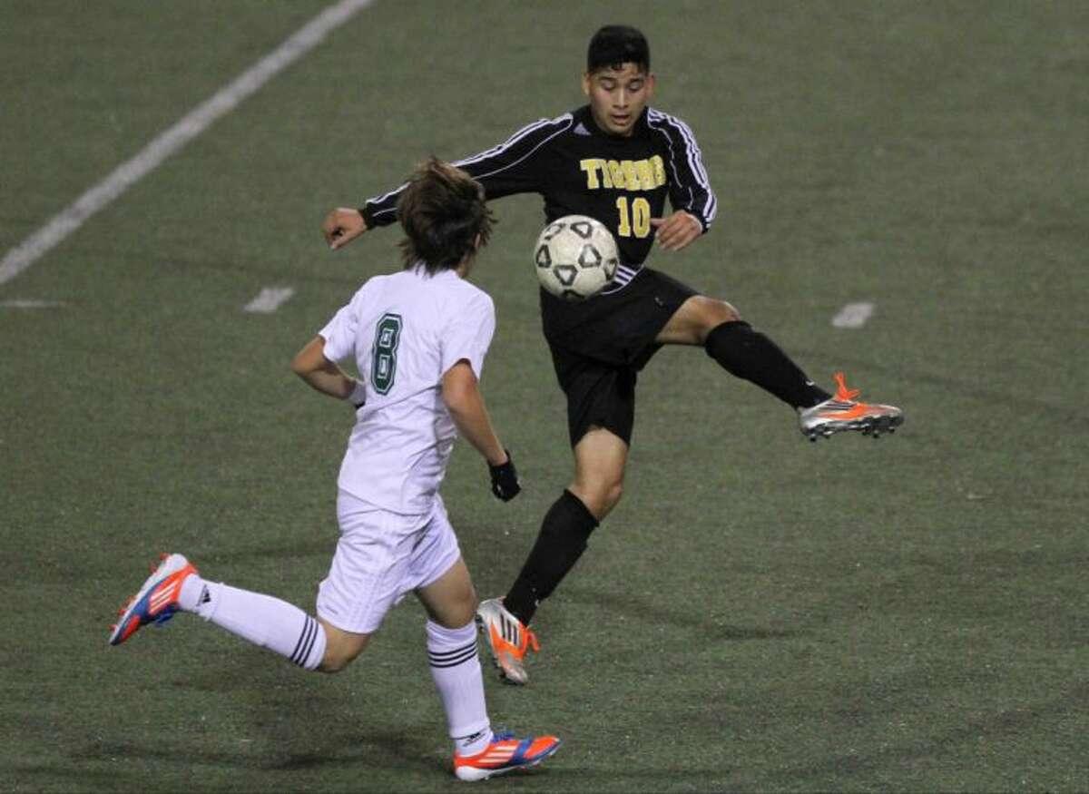 Conroe midfielder Gabriel Rivera (10) controls the ball as Cypress Falls midfielder Angel Cardona (8) defends.