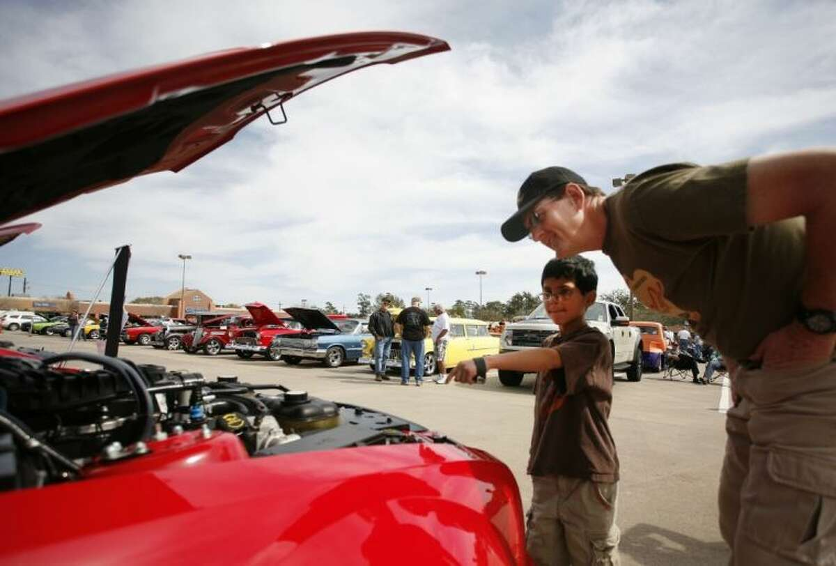 Warren Rumpel and his son Marvin, 9, check out a car display during the Cruise in Against Hunger Food Drive/Car Show on Saturday at The Outlets at Conroe. Rumpel displayed his Stingray Corvette in the show. The event was hosted by the Montgomery County Mustang Car & Truck Club. To view or order this photo and others like it, visit: HCNPics.com