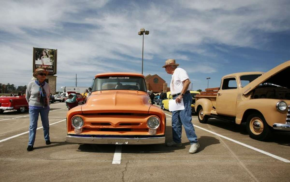 A couple check out vehicles on display during the Cruise in Against Hunger Food Drive/Car Show on Saturday at The Outlets at Conroe. The event was hosted by the Montgomery County Mustang Car & Truck Club. To view or order this photo and others like it, visit: HCNPics.com