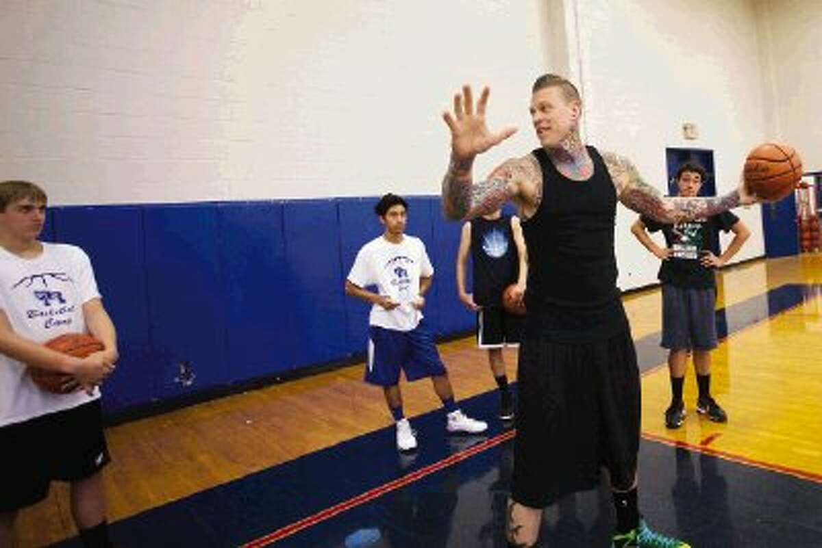 """NBA player Chris """"Birdman"""" Andersen gives instructions to campers during the Oak Ridge basketball camp on Thursday in Oak Ridge North. Andersen played for War Eagles coach Rob Stewart while both were at Iola High School."""