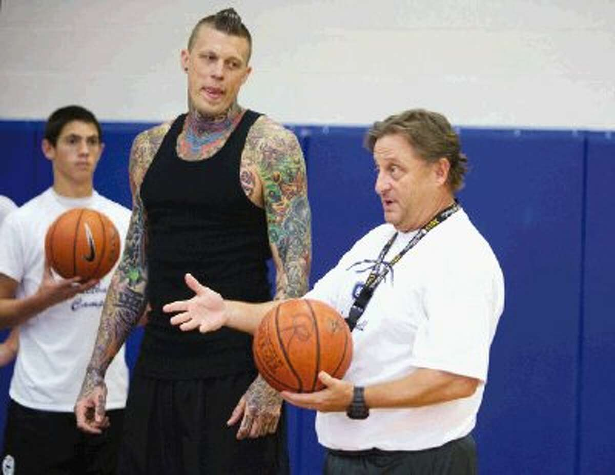 "NBA player Chris ""Birdman"" Andersen listens as Oak Ridge coach Rob Stewart gives directions to campers during the Oak Ridge High basketball camp on Thursday in Oak Ridge North."