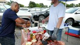 Texas State University alumnus Brushaud Callis (left) gets a barbecue sandwich from Yankee Doodle Barbecue Co. pit master and owner Peter Torrey while tailgating before the game with the University of Houston Saturday Sept. 24, 2016 at Bobcat Stadium in San Marcos, Tx.