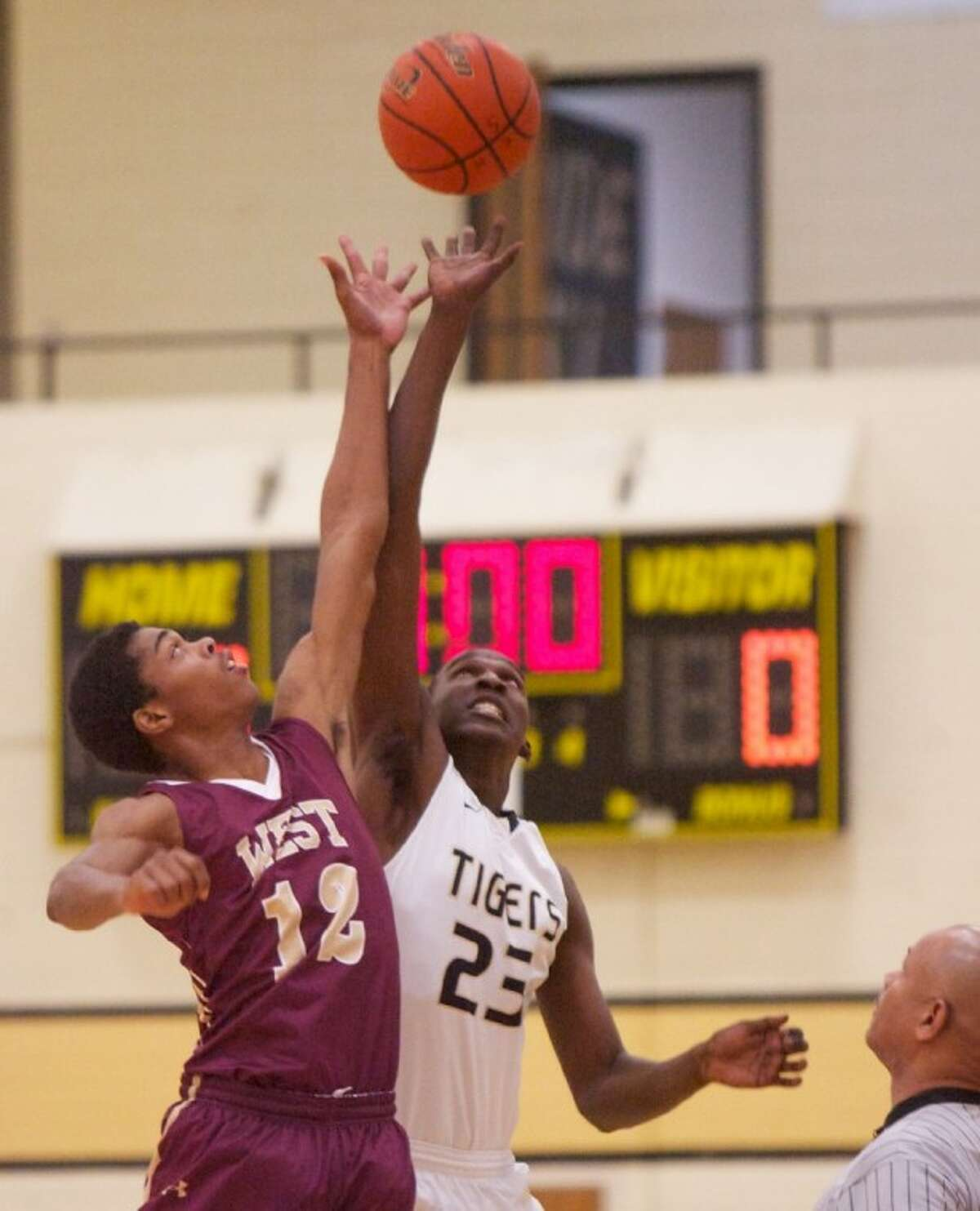Magnolia West's Zeke Bronson battles for the tipoff Thursday against Conroe's Andre Barnes during the first round of the 48th annual Conroe Christmas Classic at Conroe High School.