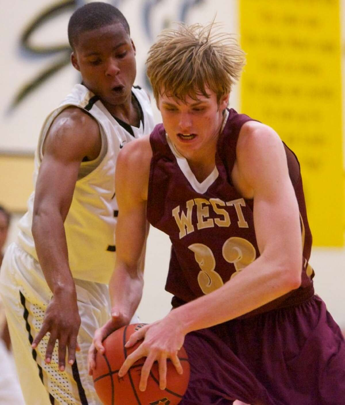 Magnolia West's Andrew Davis tries to maintain possession against Conroe's Carl Reed during the 48th annual Conroe Christmas Classic.