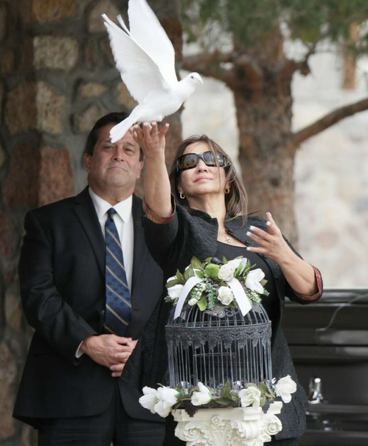 """Flora Enchinton Bernal releases a white dove during a graveside service for actor Sherman Hemsley Wednesday in Fort Bliss. Friends and family remembered Hemsley at his funeral service in Texas by showing video clips of his best known role as George Jefferson on the TV sitcom """"The Jeffersons."""" He died in July but a fight over his estate had delayed his burial."""
