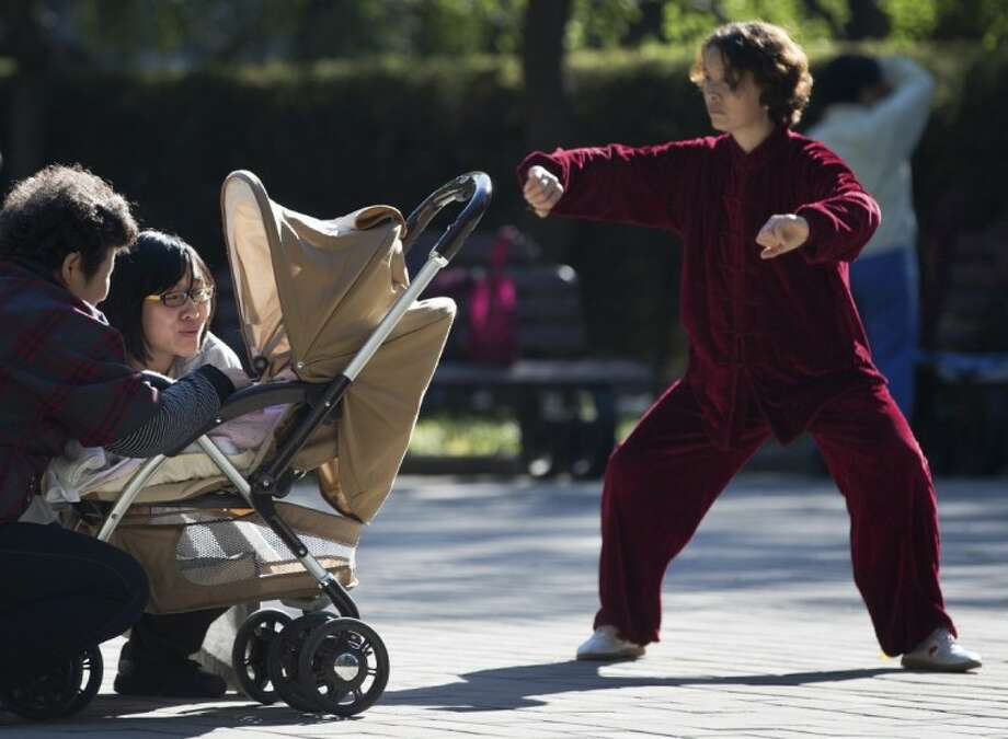 A Chinese woman performs a morning exercise next to a family members having a light moment with their infant at the Ritan Park in Beijing Wednesday. A government think tank says China should start phasing out its one-child policy immediately and allow two children for every family by 2015. It remains unclear whether Chinese leaders are ready to take that step. Photo: Andy Wong
