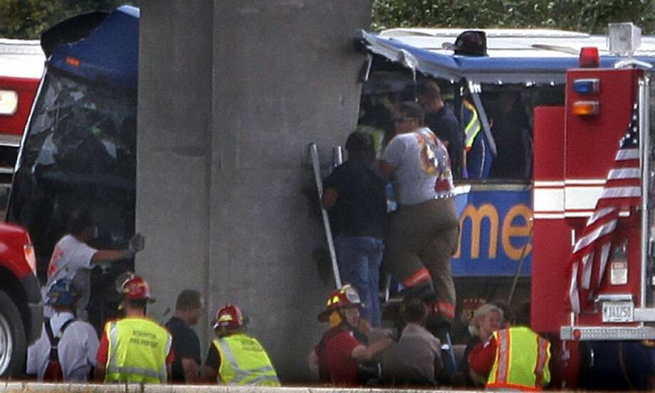 First responders work the scene of a charter bus crash on Interstate 55 near Litchfield, Ill. Thursday. The double-decker Megabus carrying 81 passengers blew a tire and slammed head-on into a concrete bridge support pillar. Four people injured in the crash were flown by helicopter to a trauma center; others were treated at local hospitals. Photo: David Spencer