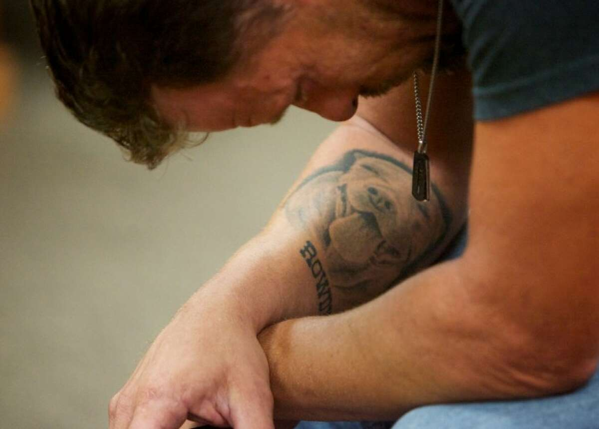 """Scott Mulanski takes a moment to reflect as he hears about the condition of dogs seized from Spindletop. A tattoo of his dog """"Rowdy"""" is seen on his forearm."""