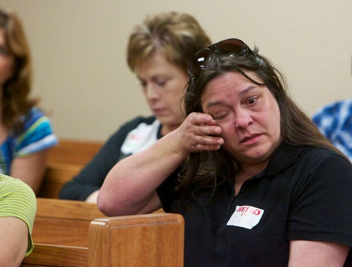 A woman wipes a tear from her eye as she learns more about the condition of dogs seized from Spindletop.