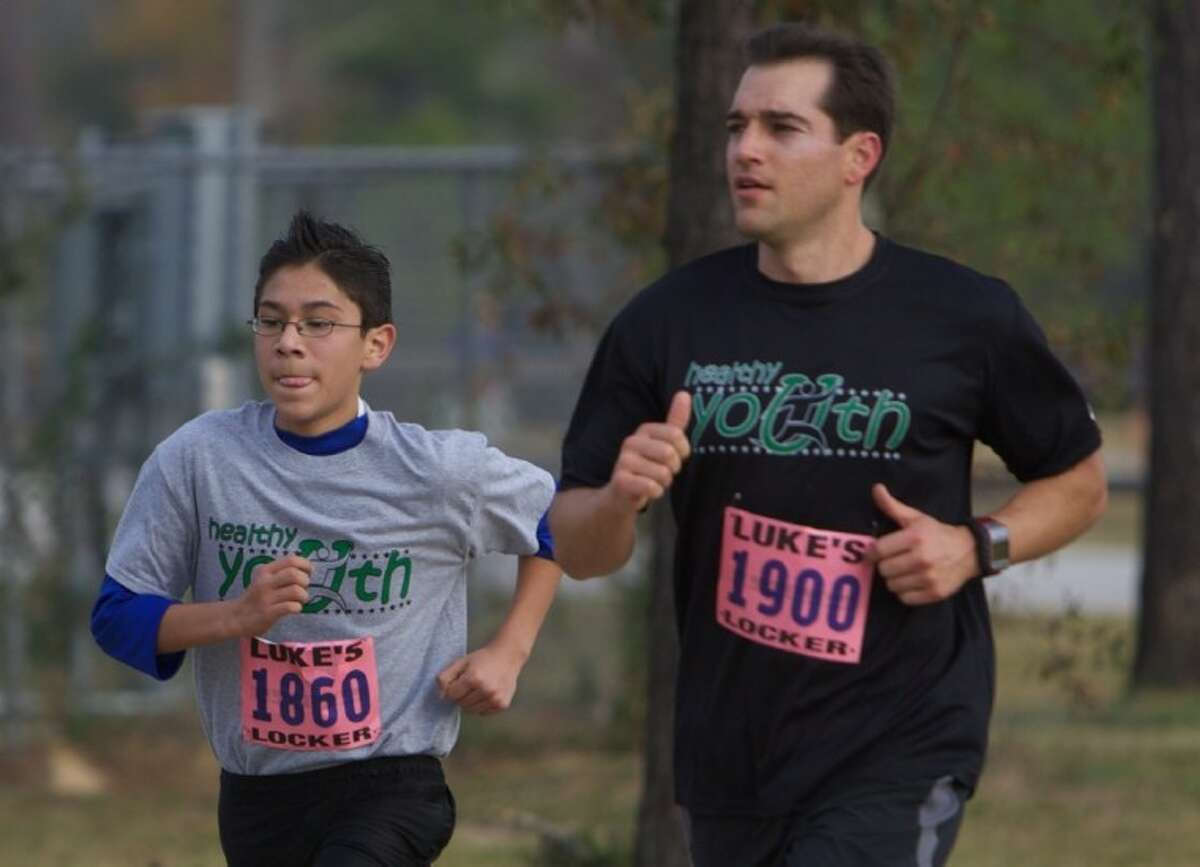 Eduardo Linares, 13, with the Healthy Youth program, runs alongside Matt Twombly, of The Woodlands, during the Eighth Annual Turkey Trot 5K Run at Carl Barton Jr. Park in Conroe Friday.