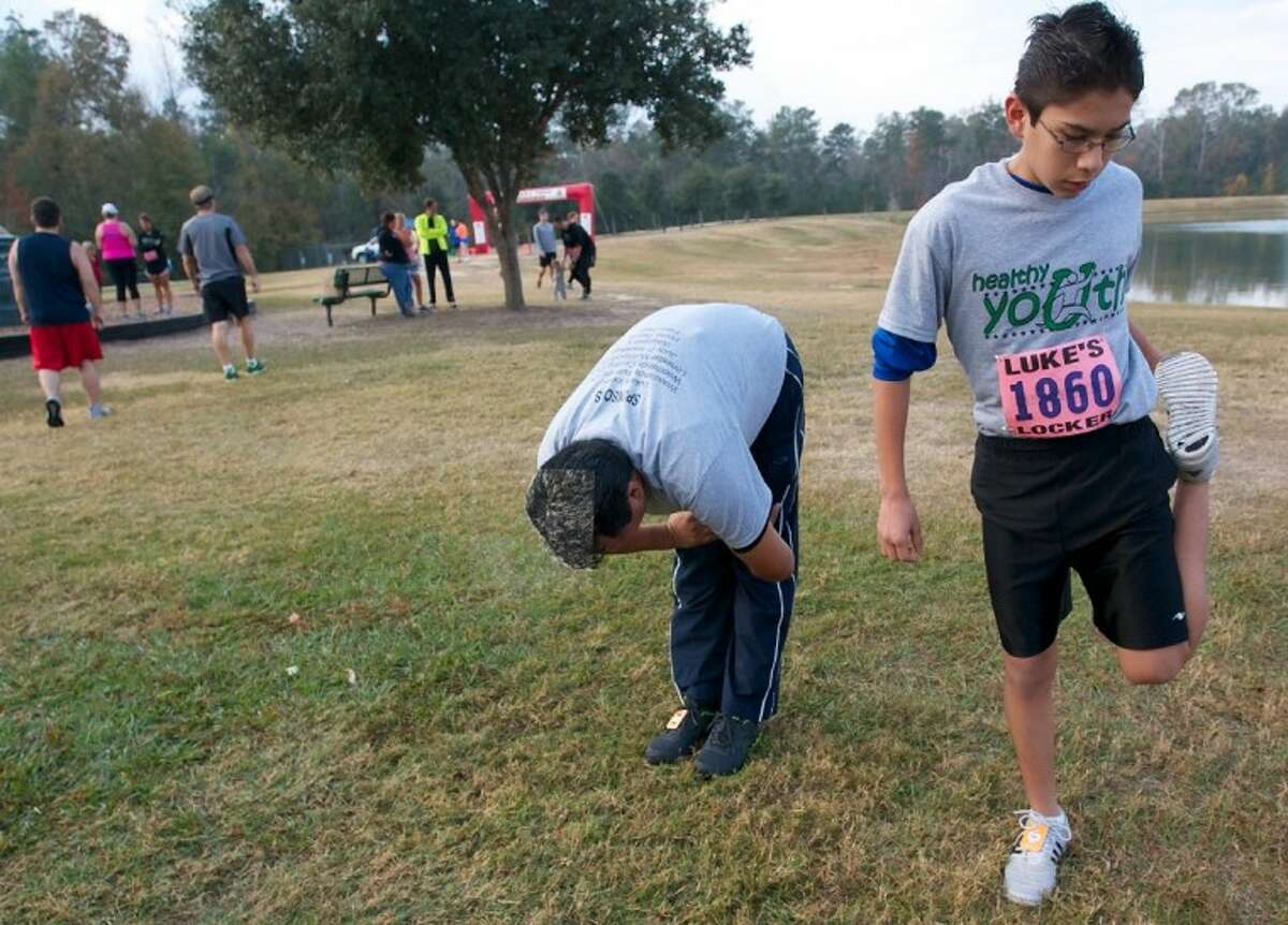 Eduardo Linares, 13, with the Healthy Youth program, stretches alongside his father Octavio, left, before the start of the Eighth Annual Turkey Trot 5K Run at Carl Barton Jr. Park in Conroe Friday.