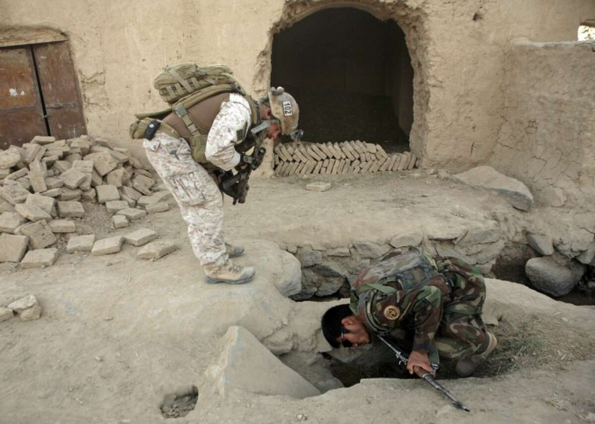 In this file photo from Oct. 31, 2009, a member of U.S. special operations forces and an Afghan National Army soldier search for roadside bombs during a joint patrol in Shewan, a former Taliban stronghold in Afghanistan's Farah province. President Hamid Karzai's office said Sunday that Afghan and U.S. officials have finalized a long-awaited strategic partnership deal. The statement from the presidency says officials from both sides have initialed the document and it is now ready to be signed by the two presidents.
