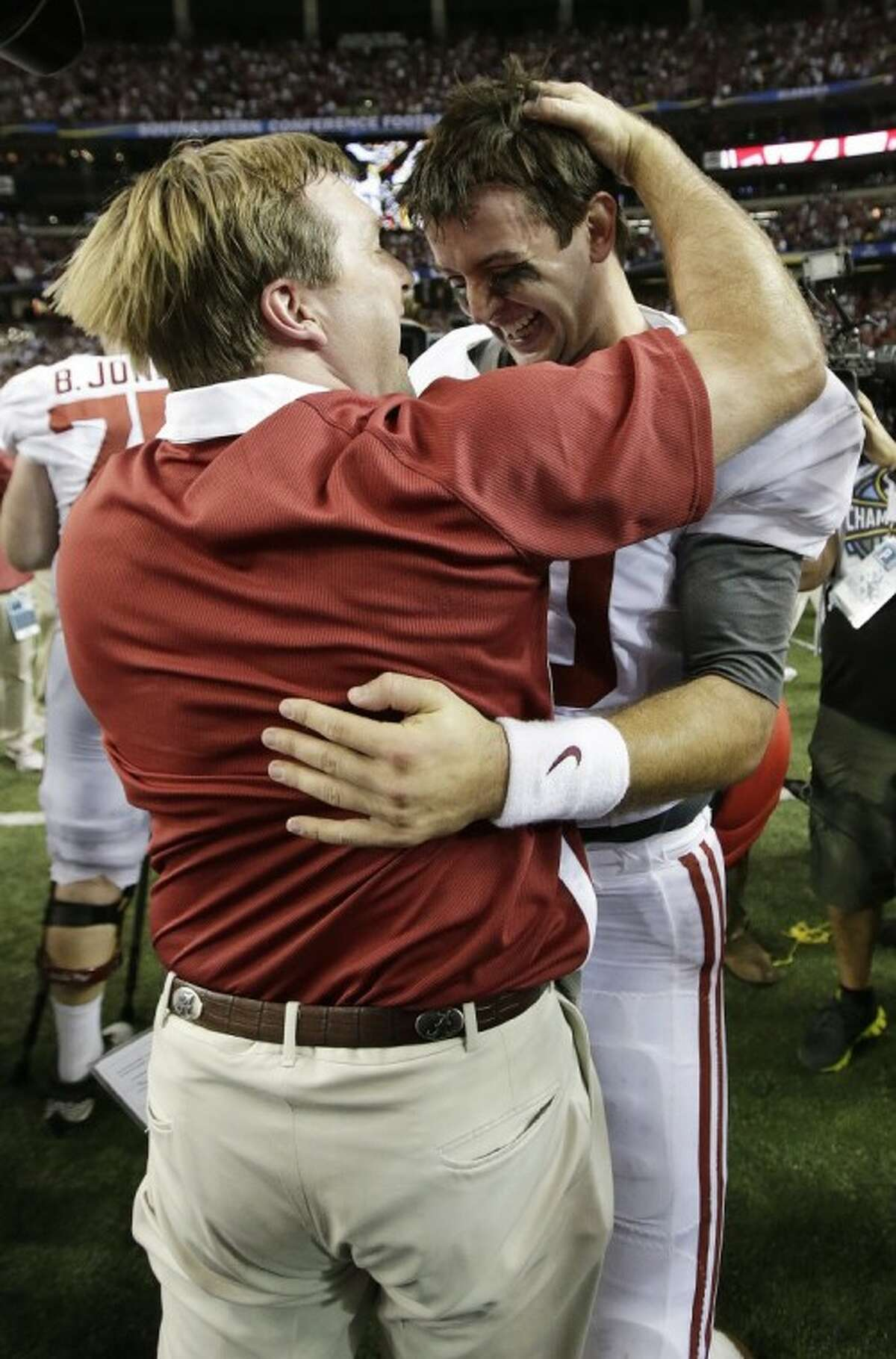 Alabama defensive coordinator Kirby Smart embraces quarterback AJ McCarron after the Crimson Tide's 32-28 win over Georgia in the SEC title game.
