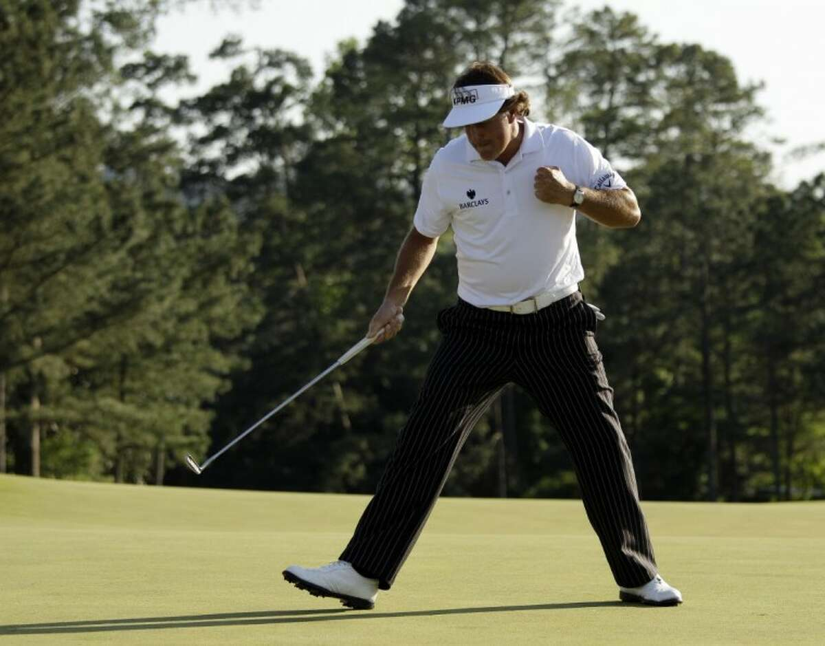 Phil Mickelson pumps his fist after a birdie putt on the 18th green during the third round of the Masters golf tournament Saturday, in Augusta, Ga.