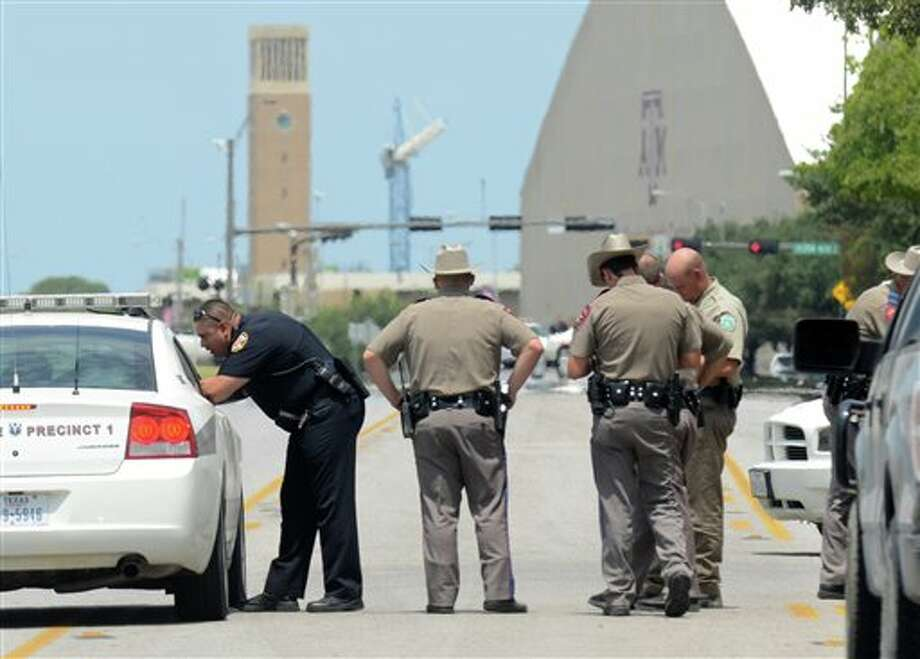 Texas State troopers and Brazos Valley lawmen work the scene of the shooting of two fellow law officers, Monday in College Station, Texas. Police say at least one law enforcement officer and one civilian have been killed in a shooting near Texas A&M University's campus. Assistant Chief Scott McCollum says the gunman also was shot Monday before being taken into custody. (AP Photo/College Station Eagle, Dave McDermand). Photo: Photo By Dave McDermand / College Station Eagle