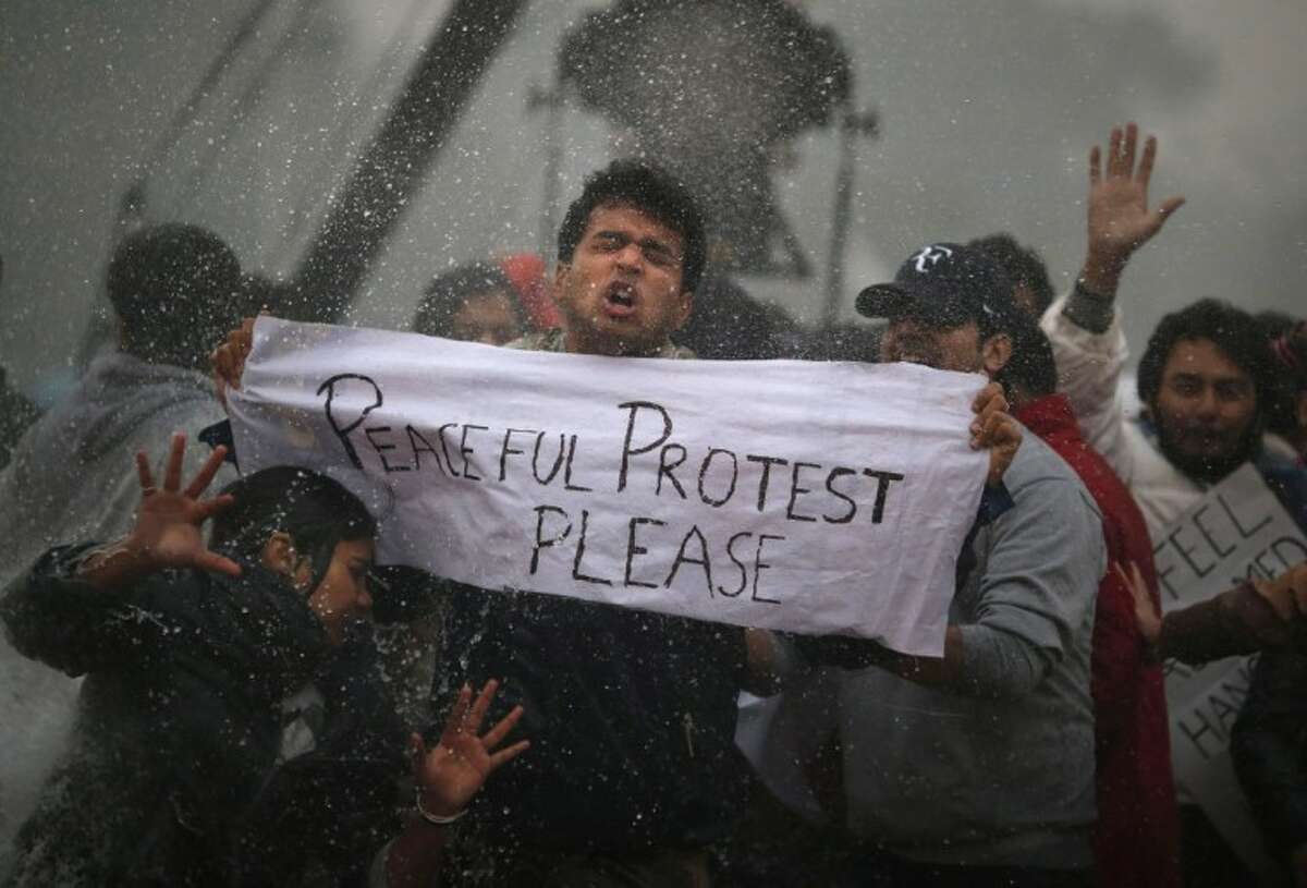 Protesters react as Indian police officers use a water cannon to disperse them near the India Gate as they protest against the gang rape and brutal beating of a 23-year-old student on a bus last week, in New Delhi, India, Sunday, Dec. 23, 2012. The attack last Sunday has sparked days of protests across the country.