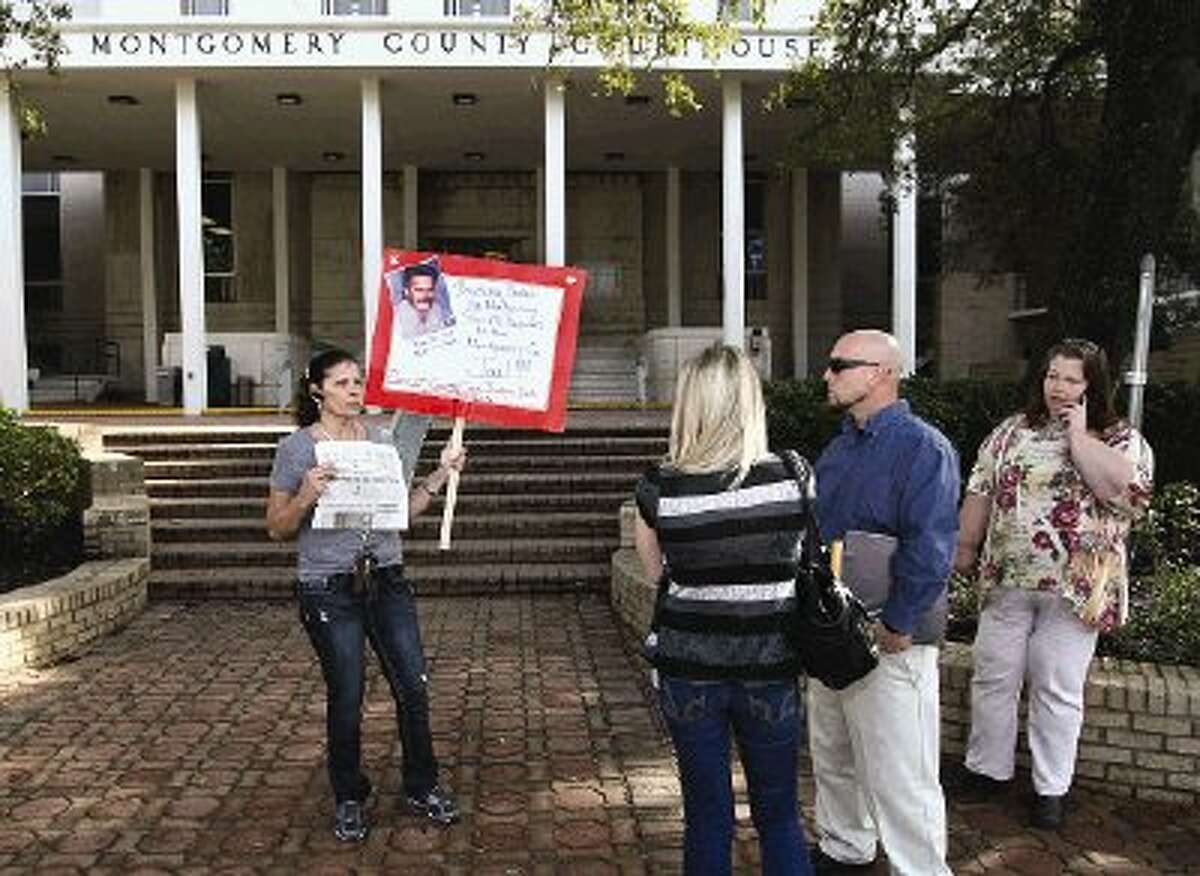 Cissy Wakat-Aikins, of Montgomery, stands in front of the county courthouse Thursday morning holding a sign about the death of her brother James Mitchell, who died in 2003 while in the county jail.