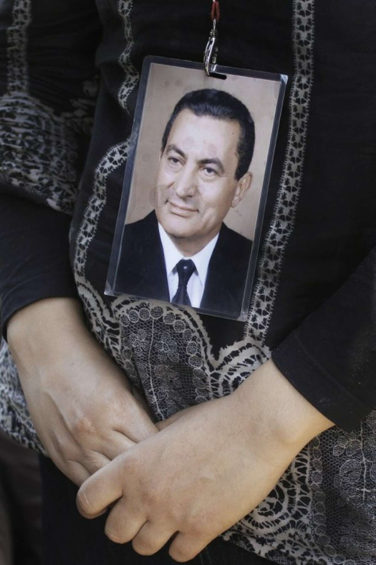 """An Egyptian woman wears a tag with a picture of ousted president Hosni Mubarak outside the Maadi military hospital in Cairo, Egypt, Wednesday. Egypt's Mubarak was on life support after suffering a stroke in prison. The 84-year-old Mubarak suffered a """"fast deterioration of his health"""" and his heart stopped beating, the state news agency MENA and security officials said."""