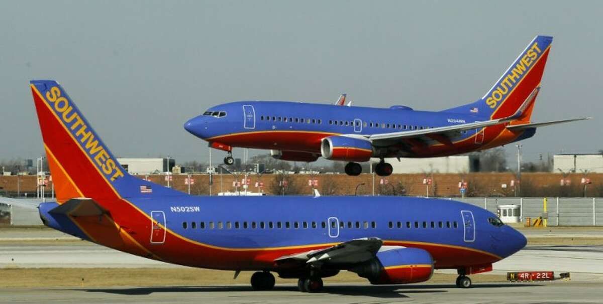 """In this Feb. 9 photo, a Southwest Airlines Boeing 737 waits to take off at Chicago's Midway Airport as another lands. Southwest Airlines' attempt to thank its online friends with a half-price ticket sale has backfired with customers inadvertently being billed multiple times, not feeling the """"luv."""" Airline spokeswoman Ashley Dillon on Saturday blamed a """"technology glitch"""" for the duplicate billings to debit and credit cards."""