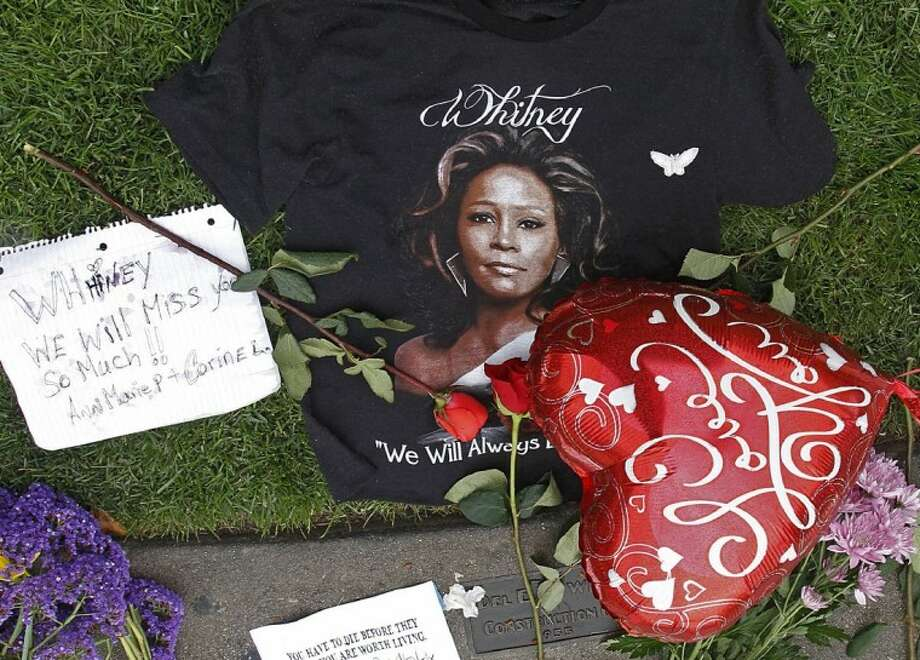 A T-shirt, flowers and notes are left at a makeshift memorial for Whitney Houston outside the Beverly Hills Hilton Hotel in Beverly Hills, Calif., on Monday. Houston, who ruled as pop music's queen until her majestic voice and regal image were ravaged by drug use, erratic behavior and a tumultuous marriage to singer Bobby Brown, died Saturday. Photo: Damian Dovarganes