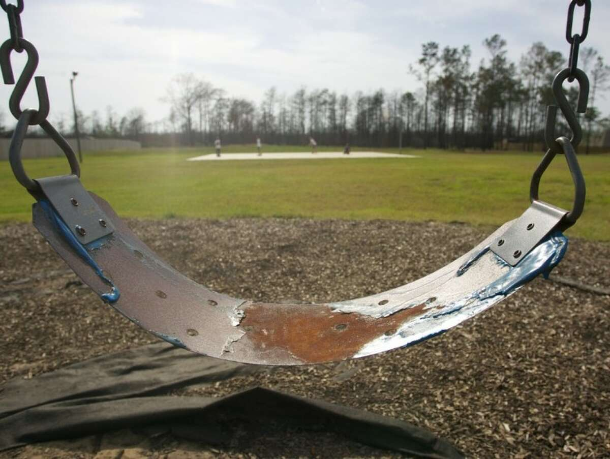 Melted plastic is still seen on a swing set t a playground which was destroyed by wildfires in Magnolia.