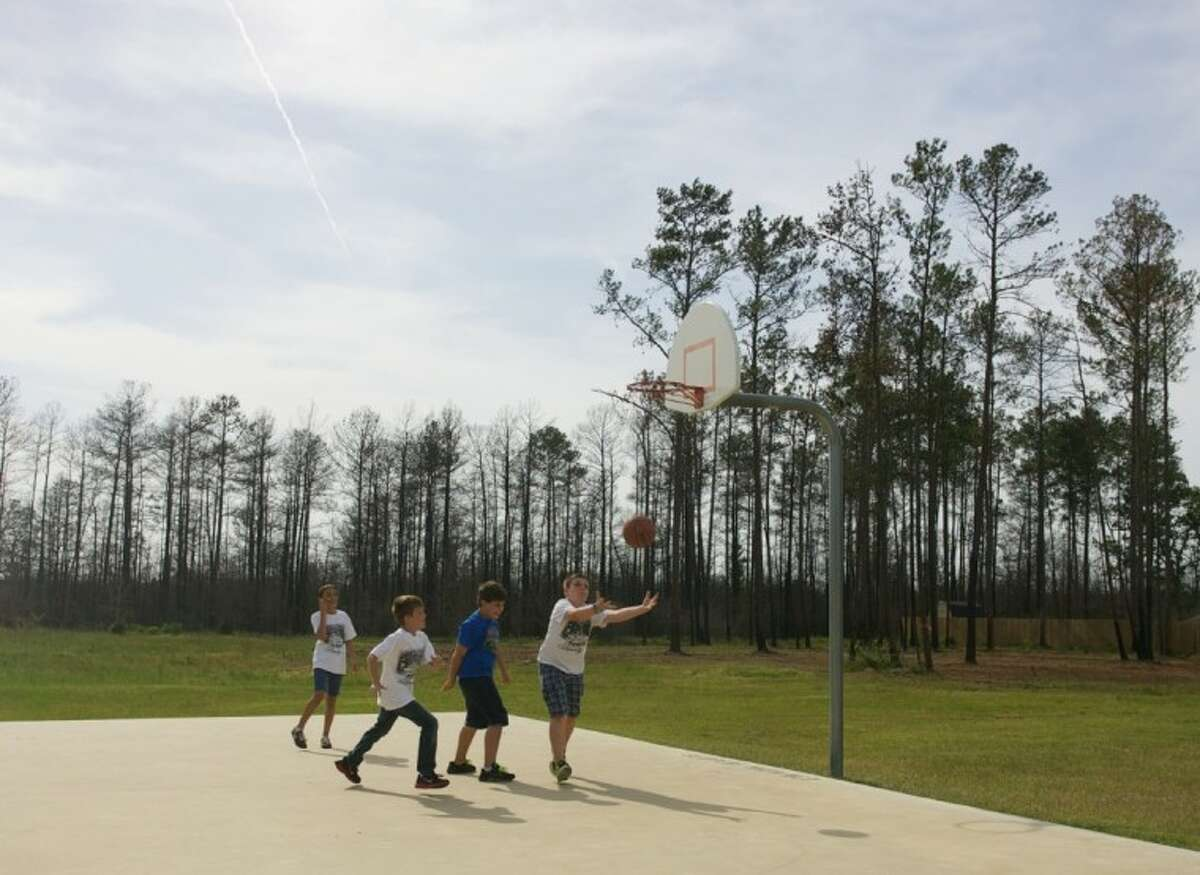 Scattered trees are seen in the distance as children play basketball. A group of children have come together to raise funds to rebuild a playground destroyed by the wildfires in Magnolia.