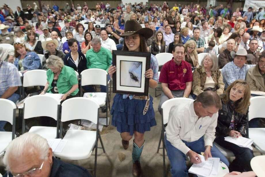 Skylar Huddleston from Morning Star 4-H shows off her grand-prize photograph during the junior non-livestock auction Monday at the Montgomery County Fairgrounds. Photo: Karl Anderson