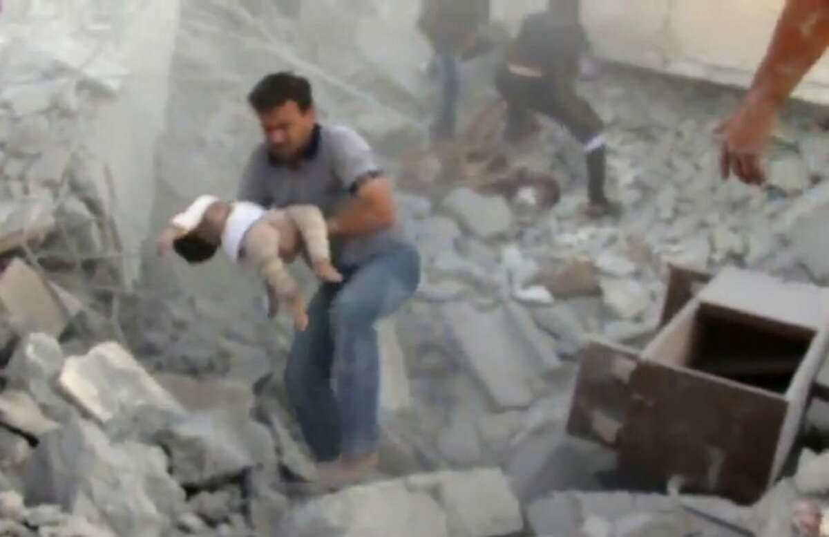 In this image taken from video obtained from Shaam News Network, which has been authenticated based on its contents and other AP reporting, a young child is rescued from the rubble of a building destroyed by government airstrike in Azaz, Syria, Friday.
