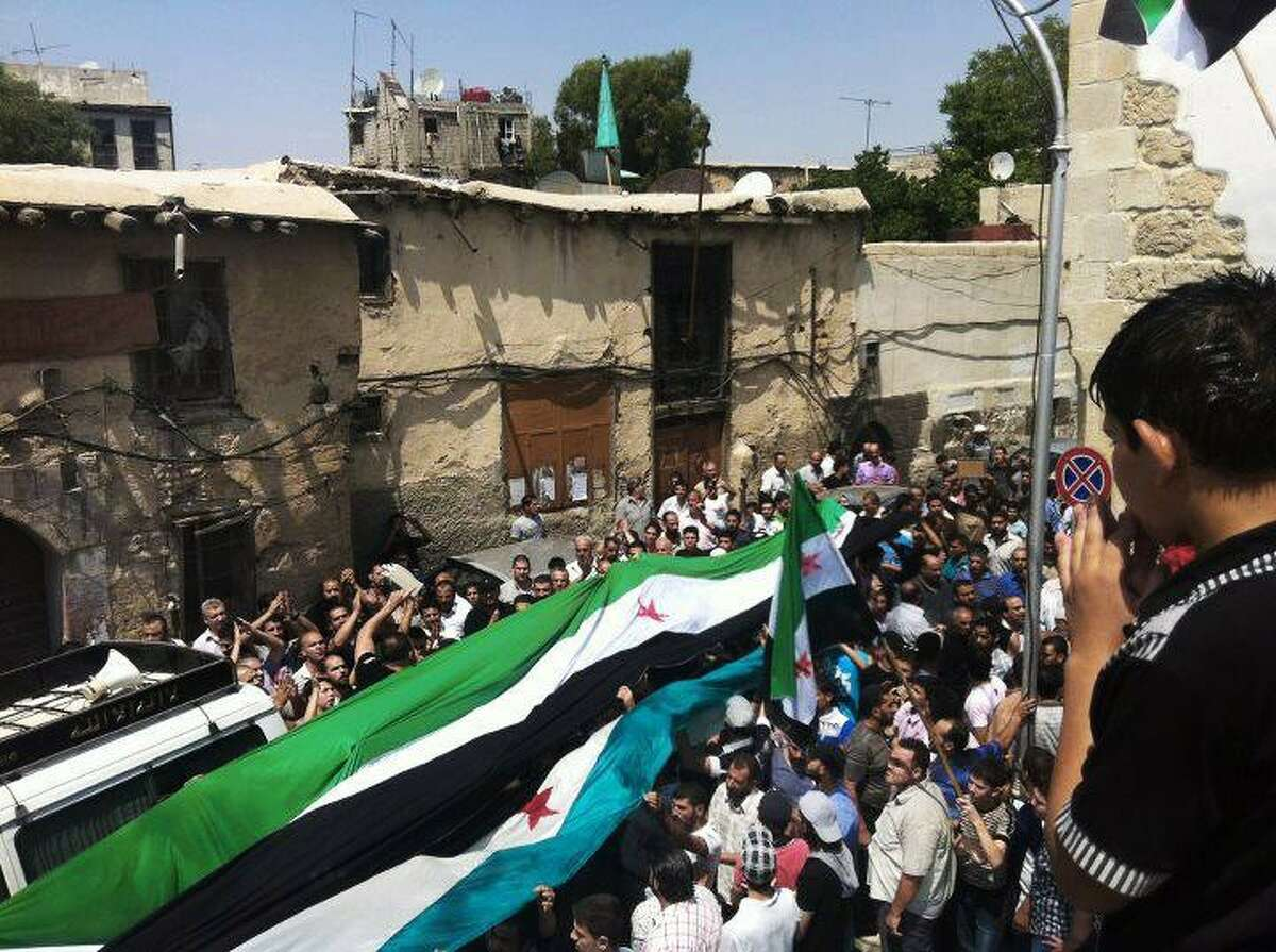 This citizen journalism image provided by Shaam News Network SNN, taken on Wednesday, purports to show Syrians holding a large Syrian revolutionary flag during the funeral procession of Mohammed al-Naan in Damascus, Syria.