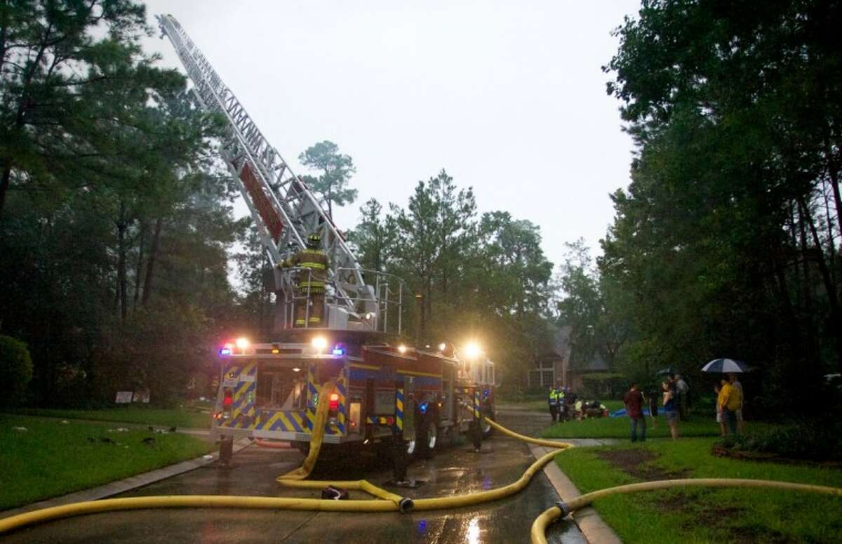 A ladder truck aids firefighters in fighting a 2-alarm residential fire thought to have been started by a lighting strike as neighbors look on Tuesday afternoon on Acadia Branch Place in The Woodlands.
