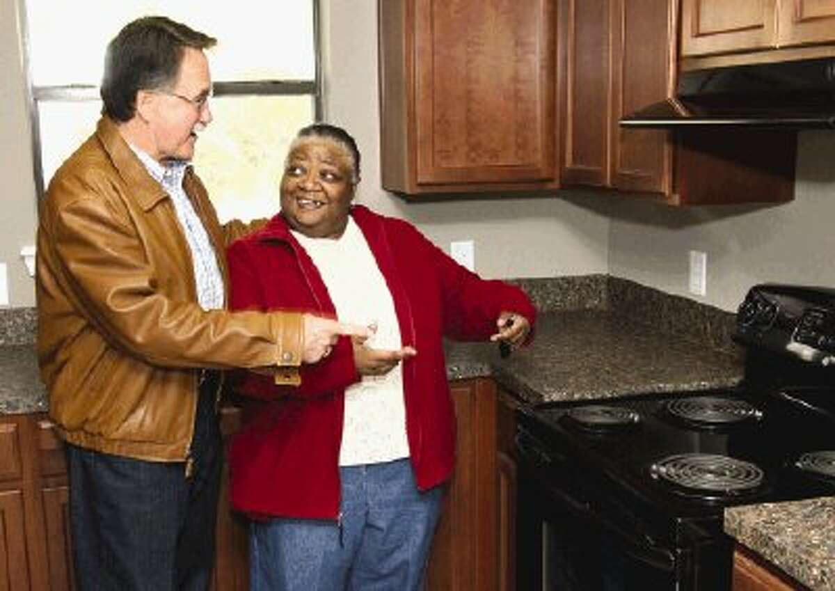 Beverly Johnson, 57, shows off the kitchen in the new home she received as part of the Community Development Block Grant program to Conroe Mayor Webb Melder.