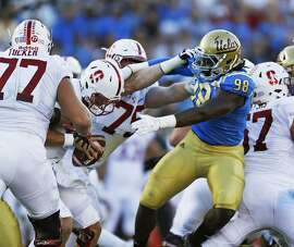 UCLA defensive lineman Takkarist McKinley (98) is held by Stanford offensive tackle A.T. Hall (75) as he tries to reach quarterback Ryan Burns in the first half at the Rose Bowl in Pasadena, Calif., on Saturday, Sept. 24, 2016. (Gina Ferazzi/Los Angeles Times/TNS)
