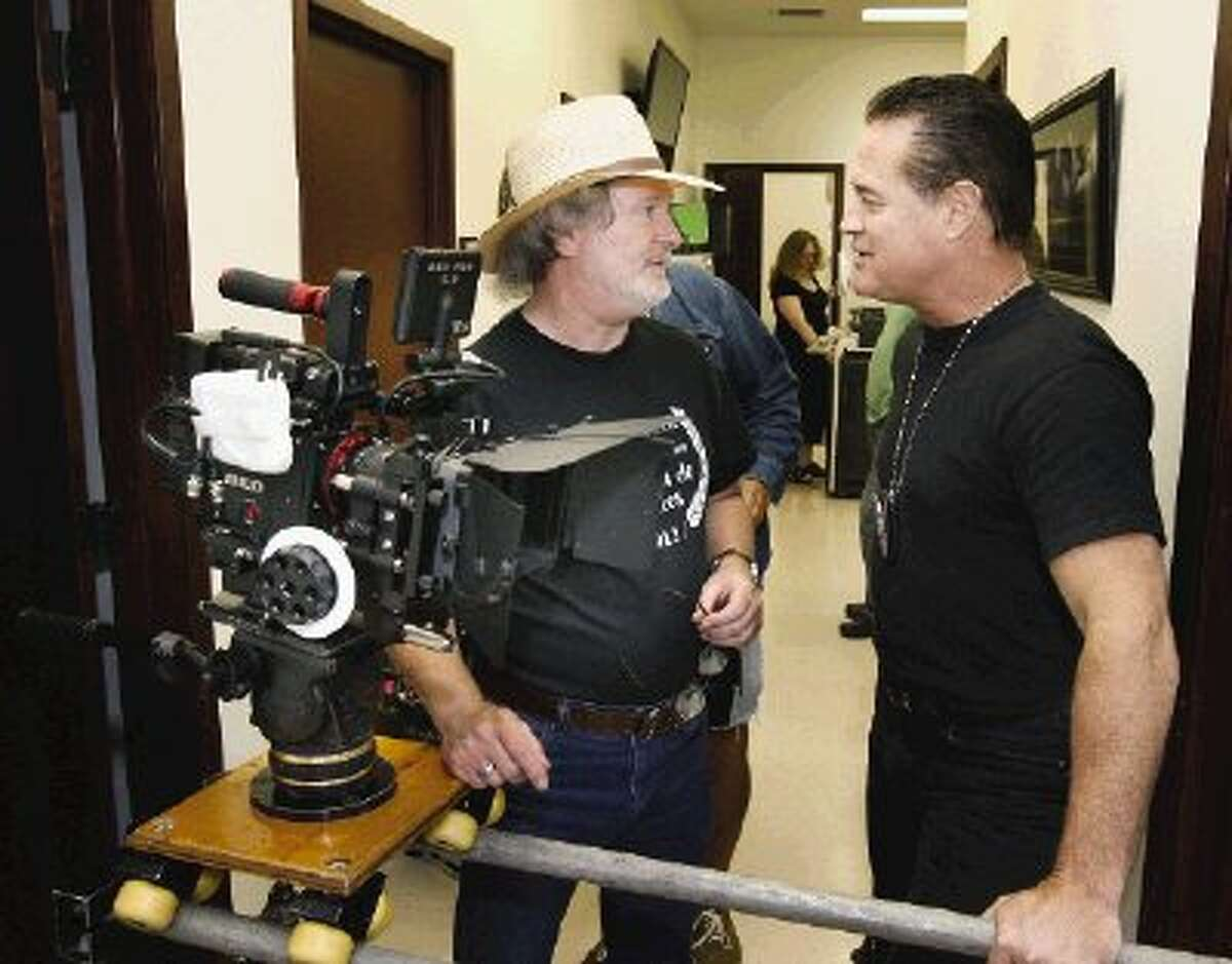 """Larry McKee, left, director of photography on """"Divorce Texas Style,"""" discusses an upcoming scene with actor and former NFL star Jim Fitzpatrick, one of the featured performers in the film."""